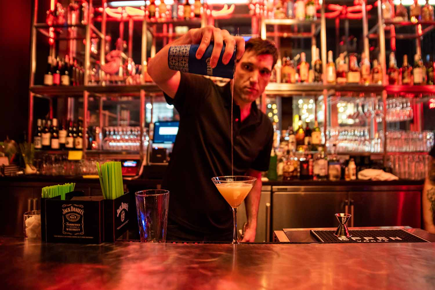 A bartender prepares a cocktail at the back bar
